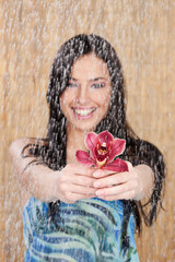 Happy girl under water drops, focus on flower