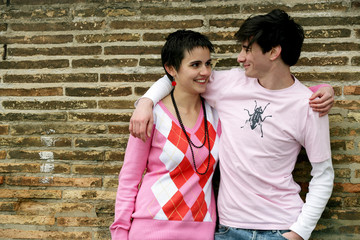 couple d'adolescents devant un mur