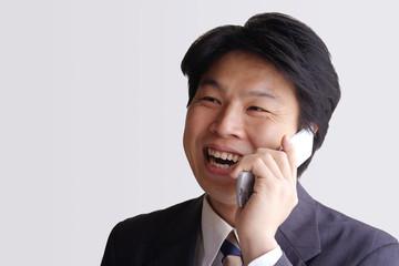 携帯電話で話す笑顔のビジネスマン
