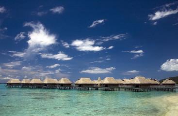 beach bungalows at tropic lagoon under blue sky