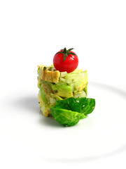 Guacamole tower with cherry tomato on white background