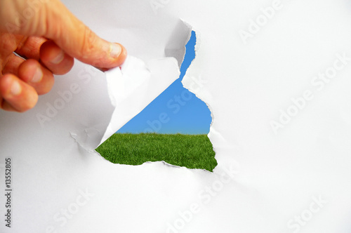 blue sky and green grass behind torn paper