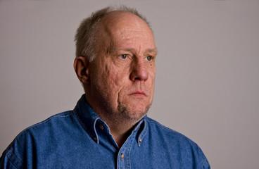 Older Bald Guy in Blue Denim Shirt Serious to Left