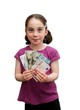 Smiling little girl with pigtails holds a fan of banknotes