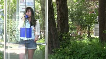Jeune fille dans une cabine téléphonique