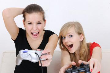 happy teenage girls playing playstation
