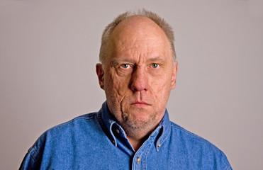 Older Bald Guy in Blue Denim Shirt Serious