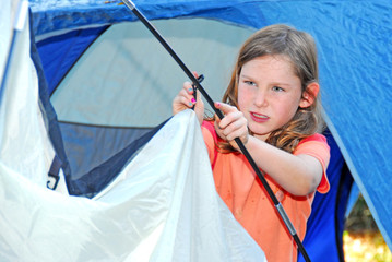 Young girl pitching tent