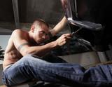 Young man fixing his car poster