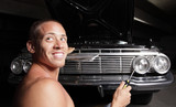 Man fixing his car with a smile on his face poster