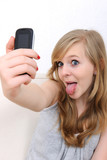 teenage girl takes a photo of herself with a cellphone poster