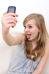 teenage girl takes a photo of herself with a cellphone