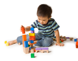 Cute preschool boy playing with wooden blocks.