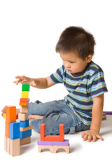 Cute preschool boy playing with wooden blocks