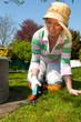 Woman working in the garden, cutting gras