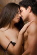 Young Man and undressing woman in love are kissing
