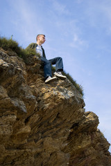 A young man sitting alone on the cliff