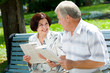 Happy elderly couple reading together outdoors