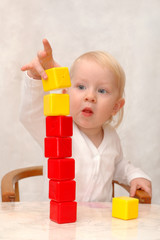 The child builds a tower of cubes