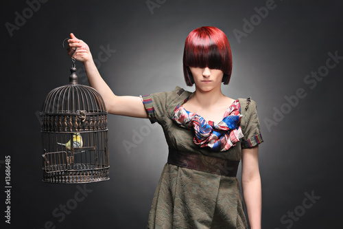 A beautiful young girl holding a birdcage with a bird inside