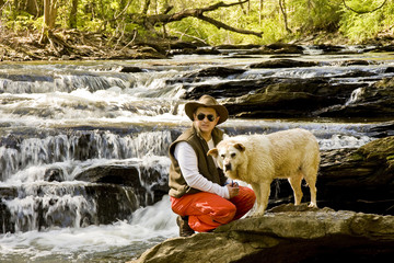 Man Knelling in River with Dog