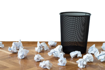 Empty wastepaper basket surrounded by crumpled documents
