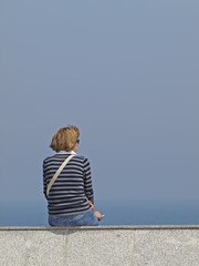 Mujer fumando frente al mar