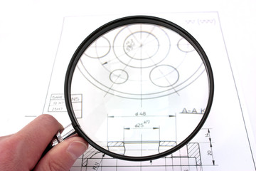 Reviewing technical drawing. Focus on magnifying glass.