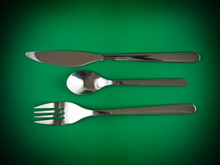 Fork, knife, spoon on green   background