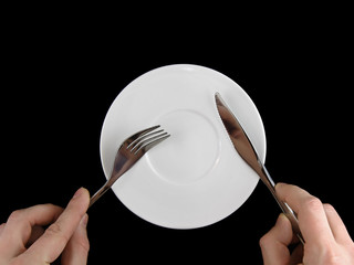 Fork, knife, spoon, plate, and hands on black  background