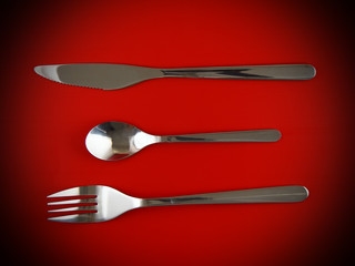 Fork, knife, spoon on red  background