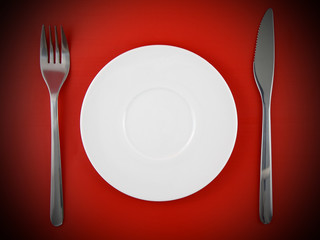 Fork, knife, plate, on red   background