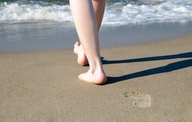 Frau läuft barfuß am Strand