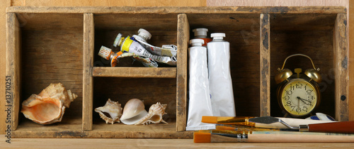 Brushes and paints on a shelf in studio of the artist