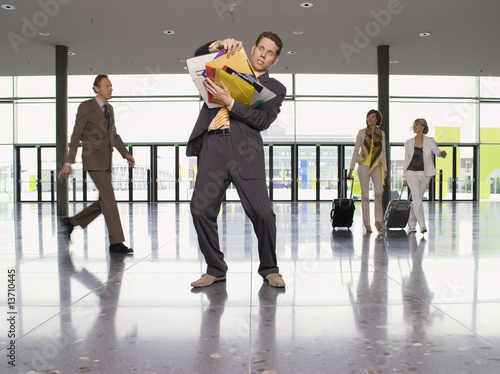 Businessman overloaded with paperwork