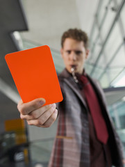 Man in suit holding penalty red card