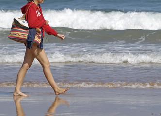 Chica caminando por la playa