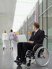 Businessman in wheelchair watching businesswomen