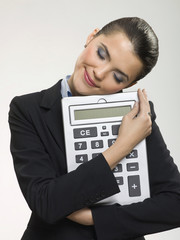 Businesswoman hugging large calculator