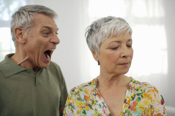 Angry senior man yelling at senior woman