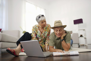 Senior couple at home looking at map and laptop