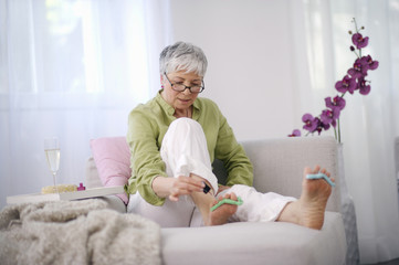 Senior woman giving herself at pedicure at home