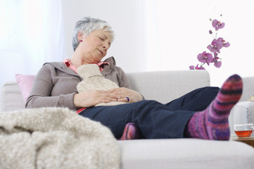 Senior woman resting at home with ice pack on stomach