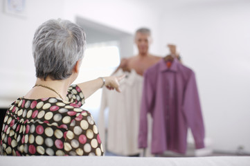 Senior woman pointing at shirts that man is deciding between