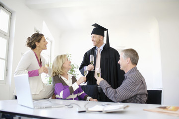 Mature people celebrating graduation with champagne