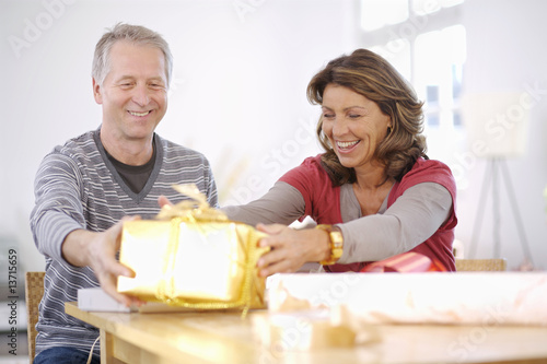 Mature couple holding shiny gift at table