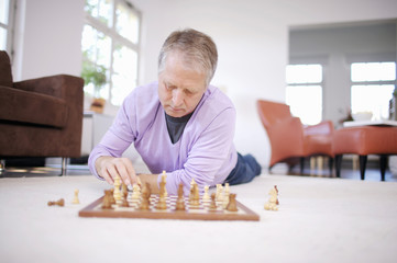 Mature man playing chess on floor at home