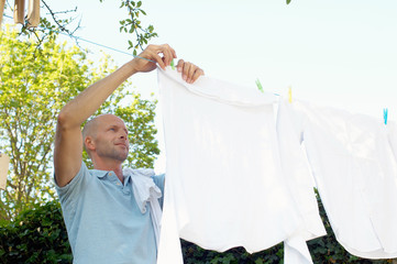 Mature man hanging clothes on washing line, low angle view, Den Haag, Netherlands