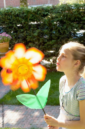 Girl blowing artificial flower, side view, Den Haag, Netherlands