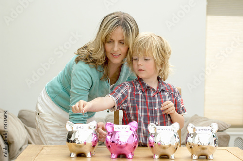 Mother and son putting coin in piggy bank, Den Haag, Netherlands